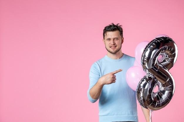 Vorderansicht junger mann mit süßen luftballons als marsch auf rosa hintergrund weiblicher frauentag sinnliches datum liebe ehegleichheit
