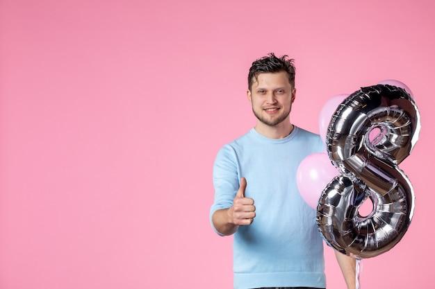 Vorderansicht junger mann mit süßen luftballons als marsch auf rosa hintergrund weiblicher gleichheit frauentag sinnliches datum liebesheirat