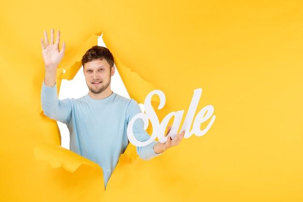 Vorderansicht junger mann mit verkaufsschreiben auf gelber wand