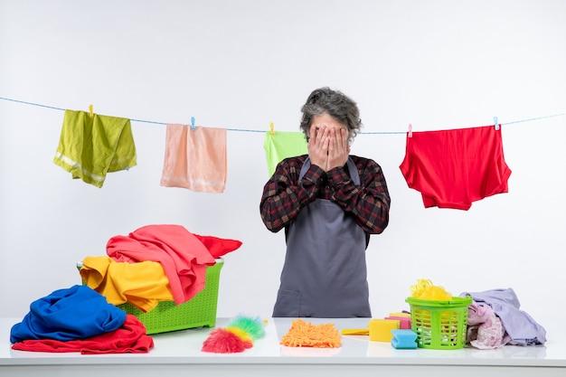 Vorderansicht junger mann mit verschiedenen sauberen kleidern und handtüchern auf weißem hintergrund