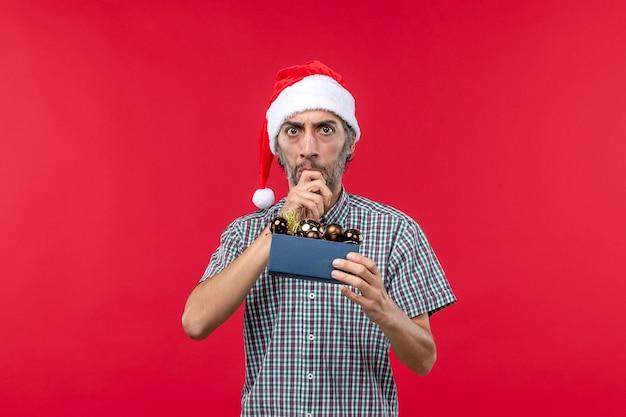 Vorderansicht junger mann mit weihnachtsbaumspielzeug auf rotem schreibtisch
