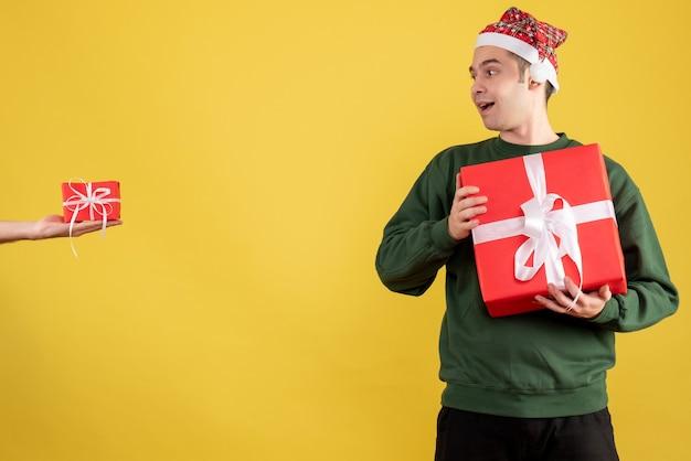 Vorderansicht junger mann mit weihnachtsgeschenk, das das geschenk in der weiblichen hand auf gelbem hintergrund betrachtet
