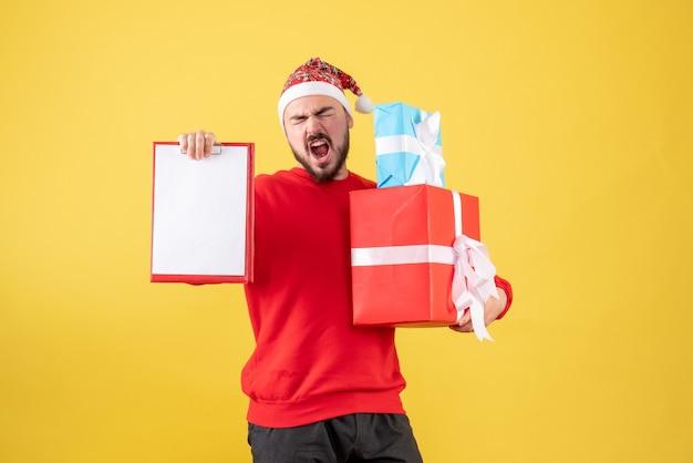 Vorderansicht junger mann mit weihnachtsgeschenk und hinweis auf gelbem hintergrund