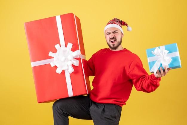 Vorderansicht junger mann mit weihnachtsgeschenken auf gelbem hintergrund