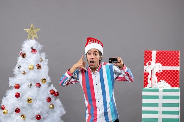 Vorderansicht junger mann mit weihnachtsmütze, die anruf mich telefonzeichen zeigt