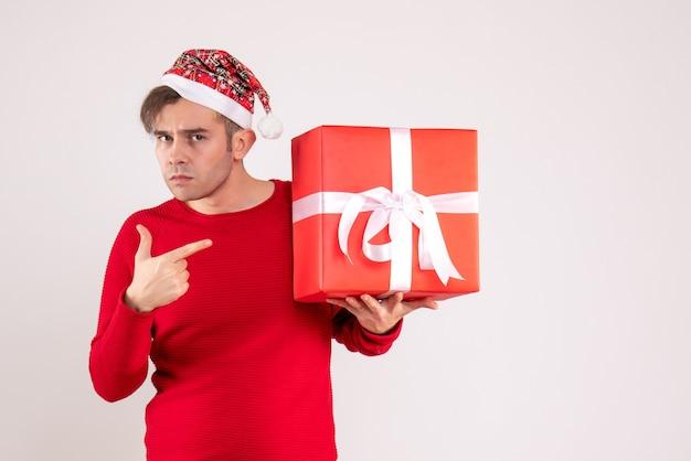 Vorderansicht junger mann mit weihnachtsmütze, die auf geschenk auf weißem hintergrund zeigt