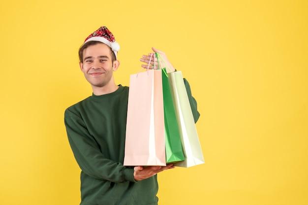 Vorderansicht junger mann mit weihnachtsmütze, die einkaufstaschen hält, die auf gelbem hintergrund stehen