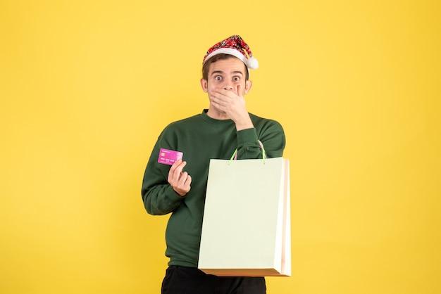 Vorderansicht junger mann mit weihnachtsmütze, die einkaufstaschen und karte hält hand an seinen mund auf gelbem hintergrund hält