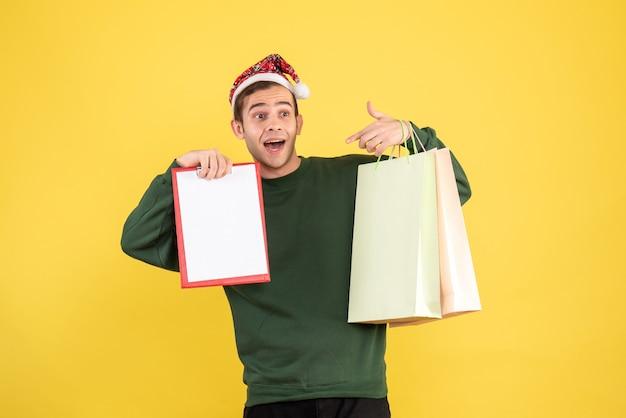 Vorderansicht junger mann mit weihnachtsmütze, die einkaufstaschen und zwischenablage hält, die auf gelbem hintergrund stehen