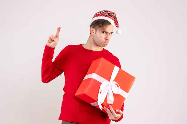 Vorderansicht junger mann mit weihnachtsmütze, die glückszeichen macht, das auf weißem hintergrund steht