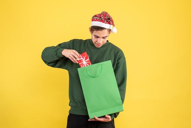 Vorderansicht junger mann mit weihnachtsmütze, die grüne einkaufstasche und geschenk hält, das geschenk auf gelbem hintergrund betrachtet