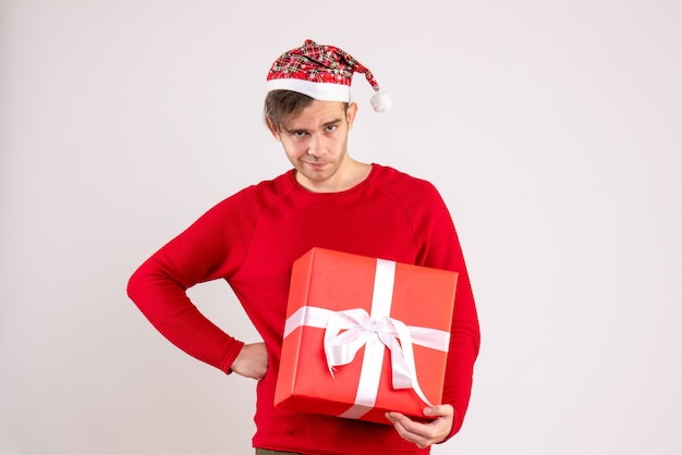 Vorderansicht junger mann mit weihnachtsmütze, die hand auf eine taille stehend auf weißem hintergrund setzt