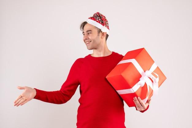 Vorderansicht junger mann mit weihnachtsmütze, die hand auf weißem hintergrund gibt