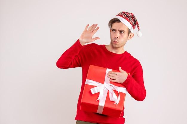 Vorderansicht junger mann mit weihnachtsmütze, die jemanden auf weißem hintergrund anruft
