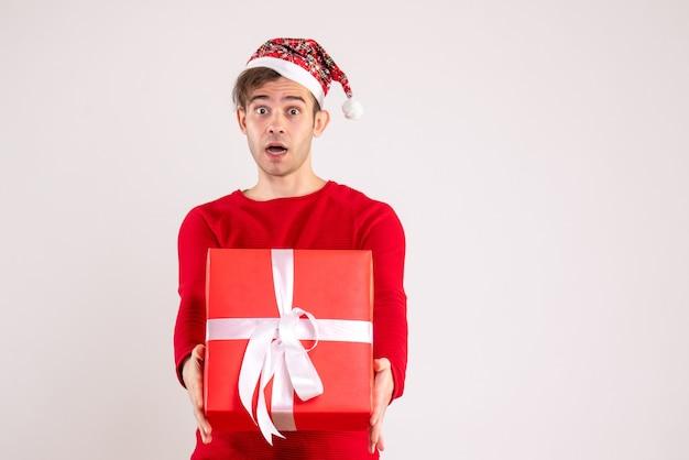 Vorderansicht junger mann mit weihnachtsmütze, die sein geschenk auf weißem hintergrund hält