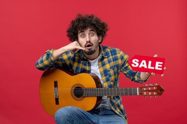 Vorderansicht junger mann sitzt mit gitarre auf einer roten wand musik farbapplaus live-musiker konzert verkauf play