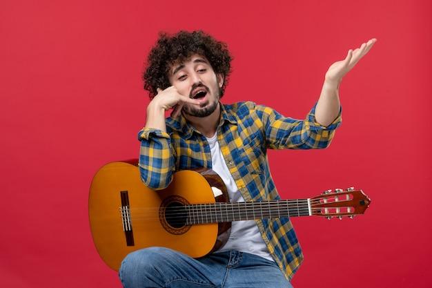 Vorderansicht junger mann sitzt mit gitarre auf roter wand applaus band konzertmusiker spielen farbe live
