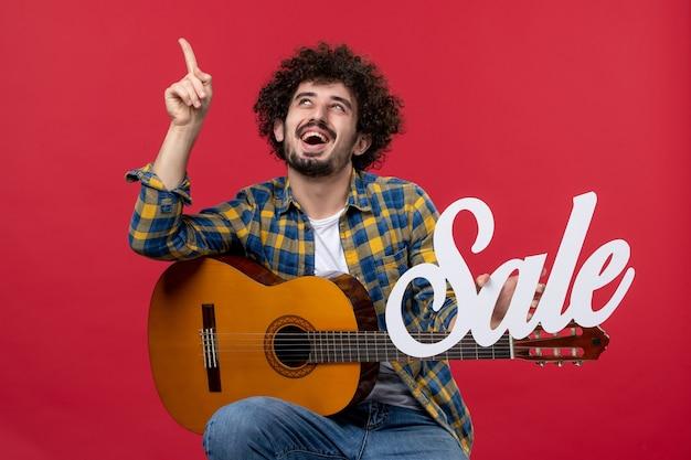 Vorderansicht junger mann sitzt mit gitarre auf roter wand spielen konzertmusiker verkauf musik farben applaus live