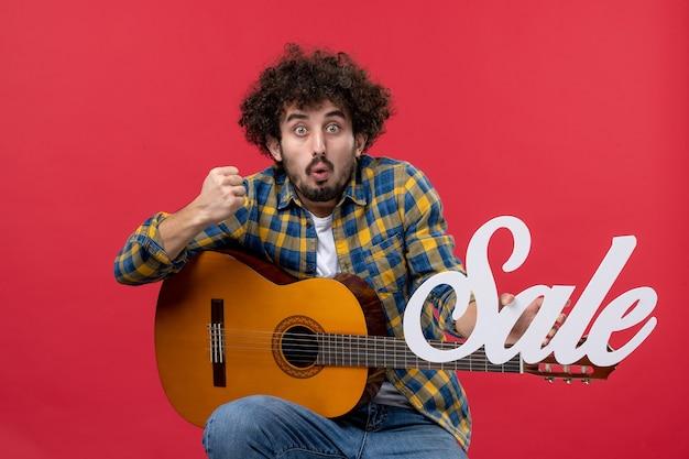 Vorderansicht junger mann sitzt mit gitarre auf roter wand verkauf spielen konzert musik farbapplaus live-musiker