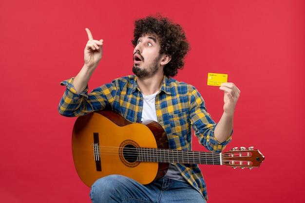Vorderansicht junger mann sitzt mit gitarre und hält bankkarte auf der roten wand musik konzert applaus musiker farbe live