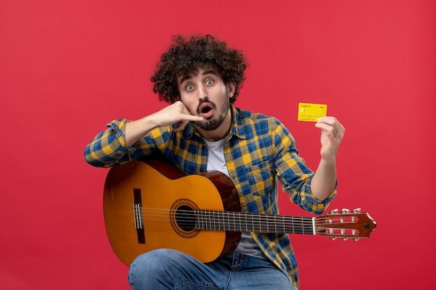 Vorderansicht junger mann sitzt mit gitarre und hält bankkarte auf roter wandmusik konzert applaus farbe live