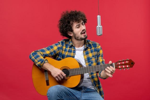 Vorderansicht junger mann sitzt mit gitarre und singt auf roter wandfarbe applaus musiker spielen konzertmusik live