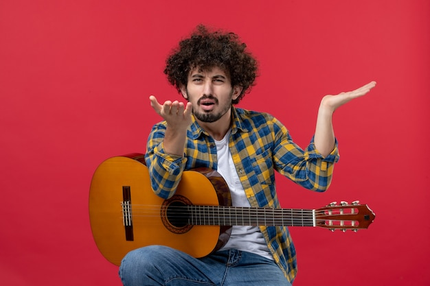 Vorderansicht junger mann sitzt mit gitarre verwirrt auf roter wand live-konzertmusiker applaus band spielt musikfarbe
