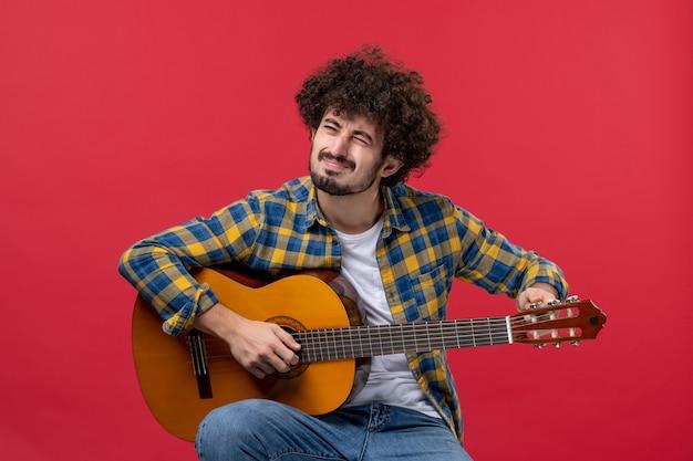 Vorderansicht junger mann sitzt und spielt gitarre auf der roten wand live-konzertmusik farbmusiker applaus band play