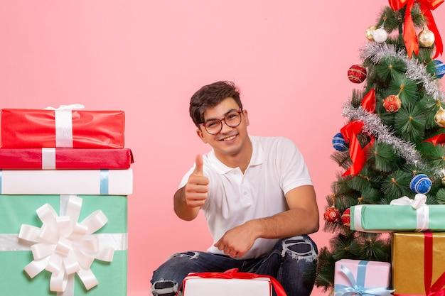 Vorderansicht junger mann um geschenke und weihnachtsbaum auf dem rosa hintergrund