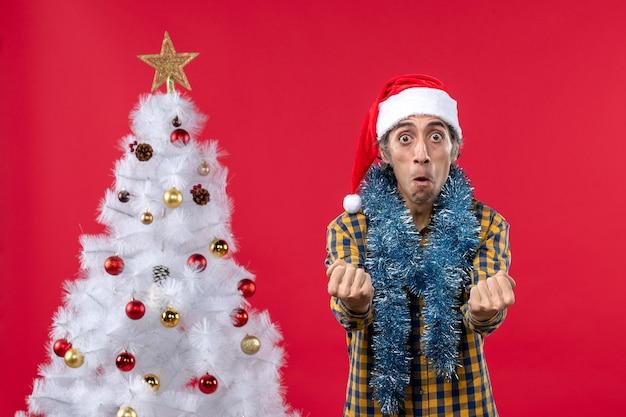 Vorderansicht junger mann um neujahrsatmosphäre auf der roten wandweihnachtsfarbfeiertag