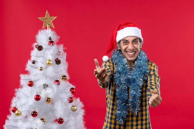 Vorderansicht junger mann um neujahrsatmosphäre auf rotem schreibtischfeiertagsweihnachtsmensch