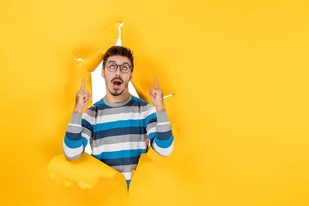 Vorderansicht junger mann zeigt mit den fingern nach oben und schaut durch zerrissene gelbe papierwand
