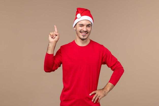 Vorderansicht junger mann zwinkert und lächelt auf braunem hintergrund männliche farbemotionsfeiertag