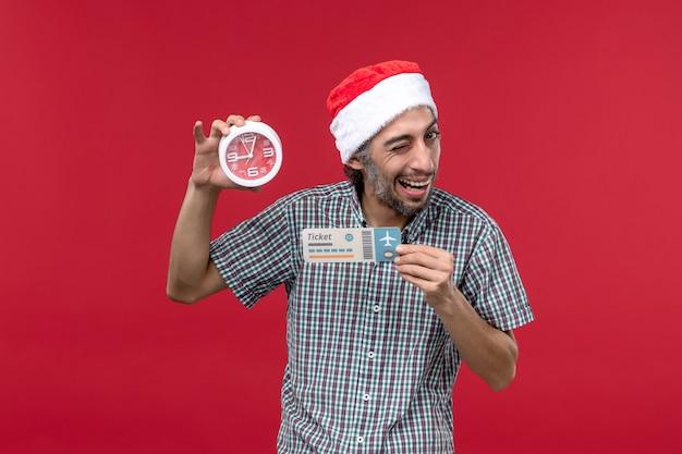 Vorderansicht junger mensch, der ticket und uhr auf rotem rotem emotionszeitmann der roten wand hält