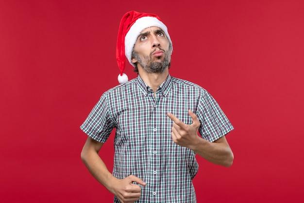 Vorderansicht junger mensch mit denkendem ausdruck auf rotem wandfeiertag neujahrsrot