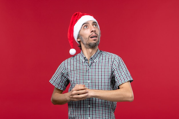 Vorderansicht junger mensch mit verwirrtem ausdruck auf rotem neujahrsfeiertag der roten wand männlich
