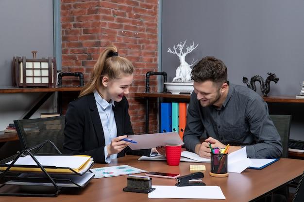 Vorderansicht junger positiver und zufriedener büroangestellter, die ein thema im dokument im büro diskutieren discuss
