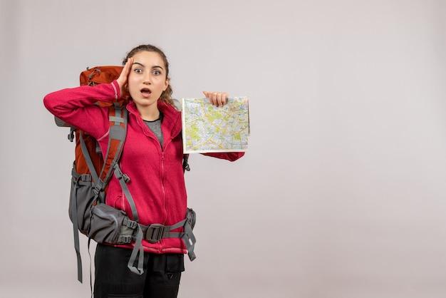 Vorderansicht junger reisender in verwirrung mit großem rucksack mit karte