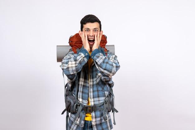Vorderansicht junger reisender mann mit rucksack, der sich wundert