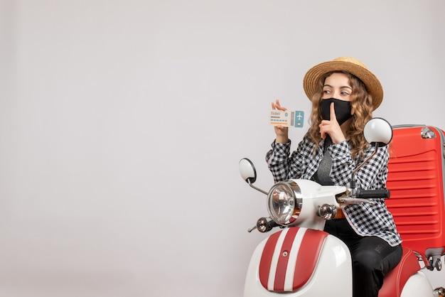 Vorderansicht junger reisender mit maske auf moped, der ein ticket hält, das stillezeichen macht?