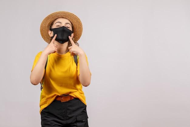 Vorderansicht junger reisender mit rucksack, der auf ihre maske zeigt