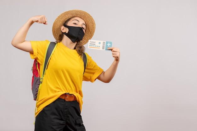 Vorderansicht junger reisender mit rucksack, der das ticket hält und armmuskel zeigt