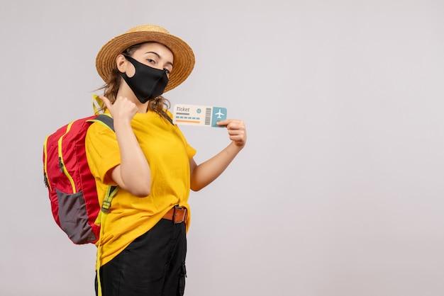Vorderansicht junger reisender mit rucksack, der das ticket hochhält und daumen hoch macht