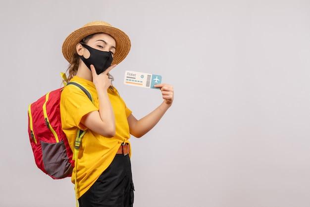 Vorderansicht junger reisender mit rucksack, der das ticket hochhält und die hand auf ihr kinn legt