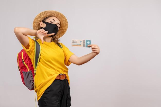Vorderansicht junger reisender mit rucksack, der das ticket hochhält