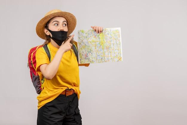 Vorderansicht junger reisender mit rucksack, der die karte hochhält und den finger nach oben zeigt