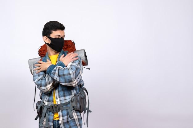 Vorderansicht junger wanderer mit rucksack und maske, die sich halten