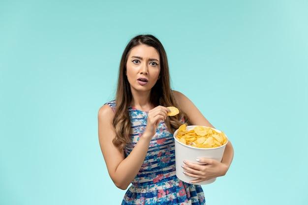 Vorderansicht junger weiblicher haltekorb mit chips auf der blauen oberfläche