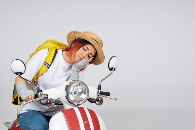 Vorderansicht junger weiblicher tourist, der auf motorrad auf weißem wandfrauen-touristenfahrgeschwindigkeitsfoto sitzt