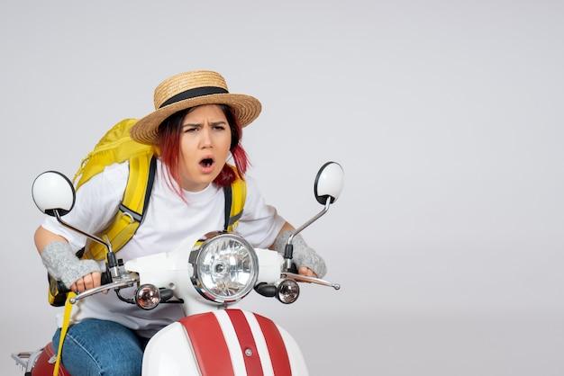 Vorderansicht junger weiblicher tourist, der auf motorrad auf weißem wandfrauen-touristenfahrzeugfoto sitzt